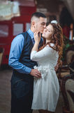Lovers young guy and girl. The young loving couple embraces and kisses. The girl in a white dress, the men in a vest. Wedding Royalty Free Stock Photography