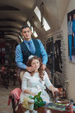 Lovers young guy and girl. The young men embraces the girl who sits in a chair at a window Royalty Free Stock Images