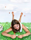 Loves me, loves me not. Teenage girs pulling petals of a daisy, while laying in a meadow Royalty Free Stock Images