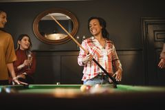 She Loves Playing Pool. Small group of female friends playing a game of pool in a games room in a house stock photography