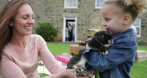 She Loves Rabbits. Little girl excited while stroking a pet rabbit ourdoors at a easter garden party