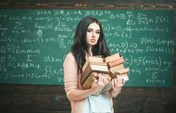 She loves reading. Girl nerd holds heavy pile of old books, chalkboard background. Girl bookworm take books in library. Student excellent fond of reading royalty free stock images