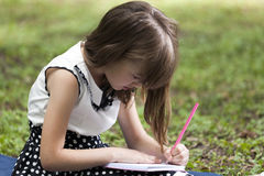 She loves to draw and write when it is in the nature. Little cute girl sitting on the grass in a park and writing in her notebook Stock Image