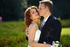 Lovesong - groom kisses a bride tenderly standing in the green p Royalty Free Stock Photos