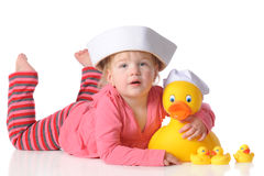 Lovey Duckie. A baby girl hugging a large rubber duck with ducklings.  Both the baby and the big duck are wearing sailor hats.  Isolated on white Stock Image