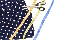 Lovez avec le fil, les ciseaux et la règle sur un morceau avec un tissu lumineux, sur un fond blanc Photos libres de droits