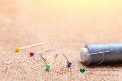 Lovez le fil avec une aiguille coincée dans elle à côté des goupilles de tailleur dessus Photographie stock libre de droits