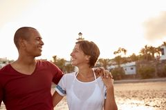 Loving adult couple in an embrace. Loving adult couple on the beach with their arms around each other and eyes locked together with a clear white sky behind them royalty free stock photos