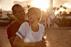 Loving adult couple cackling with laughter. Loving adult couple in front of a lighthouse in a loving embrace cackling with laughter with the sun setting behind royalty free stock photo