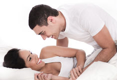Loving affectionate couple in bed Stock Images