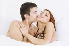 Loving affectionate couple on bed Stock Photography