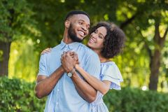 Loving african-american couple hugging in summer park. Loving african-american couple hugging while walking in summer park royalty free stock photography