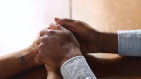 Loving african husband holding hands of wife give support, closeup