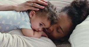 Loving African mommy hugging soothing adorable baby boy in bed