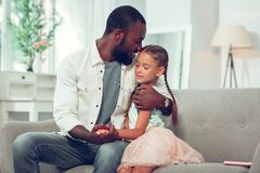 Loving Afro-American father tenderly hugging lovely pretty small daughter. Loving father with small daughter. Loving handsome nice-appealing Afro-American stock image