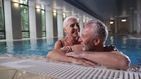 Loving aging couple relaxing in pool of spa hotel stock video