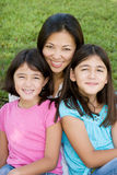 Loving Asain mother and her daughters smiling. Royalty Free Stock Images