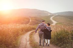 Loving attractive middle-aged couple walking away on the road. stock photos