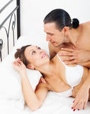 Loving awaking couple in bed Royalty Free Stock Photos