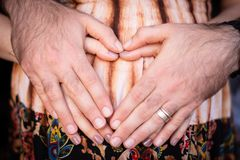 Loving Baby coming soon. Hands and Heart. Daddy and Mommy. Newborn Royalty Free Stock Image