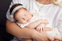 Loving babygirl sleeping in mother`s hands. Closeup picture. Hap royalty free stock images