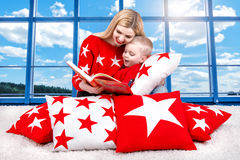 Loving beautiful young mother reads a book to his little son. Lying on the pillows for interior decoration in the background of th Stock Image