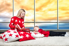 Loving beautiful young mother reads a book to his little son. Lying on the pillows for interior decoration in the background of th. The concept of a family royalty free stock photos