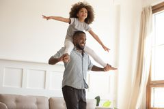 Loving black dad giving little daughter piggyback ride at home. Loving black dad giving cute little kid daughter piggyback ride at home, happy african american stock photos