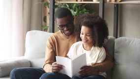 Loving black father embrace kid daughter reading book at home