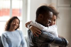 Loving black father embrace little daughter at home stock photos