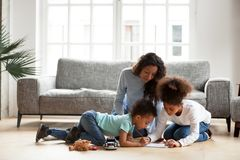 Loving black mom and little children drawing with colored pencil royalty free stock photos