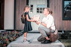 Loving blonde-haired father making little surprise for his cute schoolgirl royalty free stock images