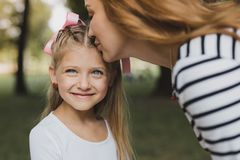 Loving blonde-haired mother kissing her cute preschool girl royalty free stock images