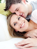 Loving boyfriend hugging his girlfriend on a sofa. Portrait of a loving boyfriend hugging his girlfriend on the sofa in the living room stock images