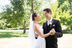 Loving bride and groom dancing in garden. Young loving bride and groom dancing in garden Stock Photo