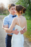 Loving bride and groom embrace on the road in park Stock Photos