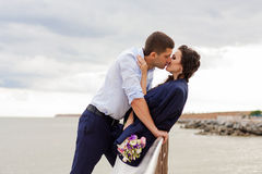 Loving bride and groom kissing on the pier. Royalty Free Stock Photo