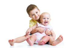 Loving brother and little sister hugging isolated Stock Photos
