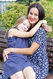Loving brunette mother and blond daughter stock photos