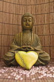 Loving Buddha 02. Brown buddha sculpture and a green heart stock photography