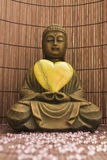 Loving Buddha. Brown buddha sculpture and a green heart royalty free stock photography