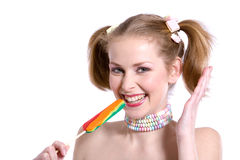 Loving the candy. Pretty blond girl with ponytails laughing with a candy cane Royalty Free Stock Photography