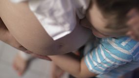 Loving and careful son with pregnant mother. Top view of son hugging pregnant mother and kissing her belly. Child is eager to have junior brother or sister stock video footage