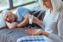 Cheerless aged woman holding pills for her husband. Loving caregiver. Pleasant aged woamn holding pills for her husband who is feeling sick and sleeping in the Royalty Free Stock Image