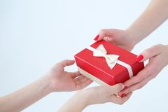 Loving family hands present gift box celebration. Loving and caring family relationship. hands holding present in a red gift box with a bow. birthday or royalty free stock images