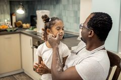 Loving caring father cleaning face of his beautiful girl stock images