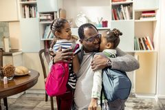 Loving caring father hugging his cute little girls going to school. Little girls. Loving caring father hugging his cute little girls with backpacks going to royalty free stock image