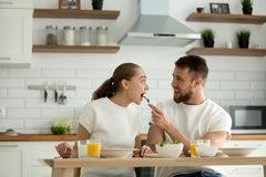 Loving caring husband feeding wife enjoying healthy meal on brea. Affectionate young couple having breakfast or dinner eating together at home sitting at kitchen Royalty Free Stock Photo