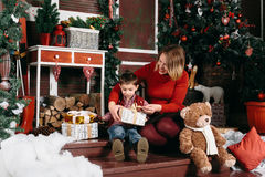 Loving Christmas traditions. Mother giving a present to her little son. Beautiful women gives a gift to his son royalty free stock photography