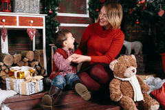 Loving Christmas traditions. Mother giving a present to her little son. Beautiful women gives a gift to his son. Boy and women smile at each other Stock Image